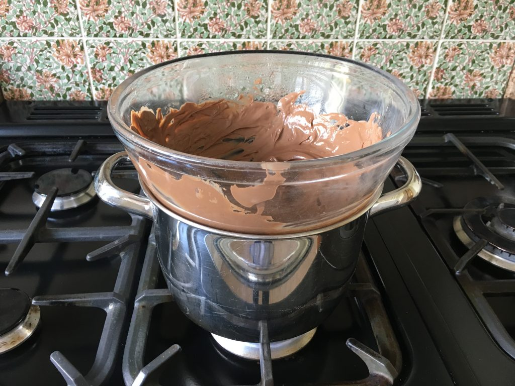 Melting cadburys chocolate buttons for magic mallow crispy cakes