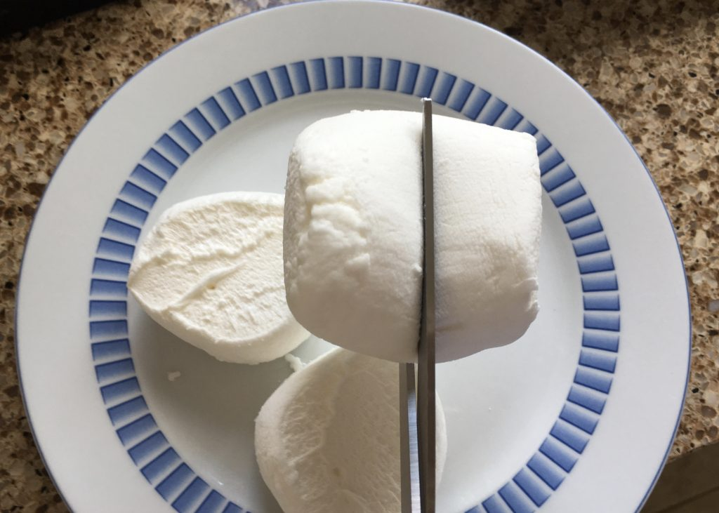 Cutting a large marshmallow in half for magic mallow crispy cakes
