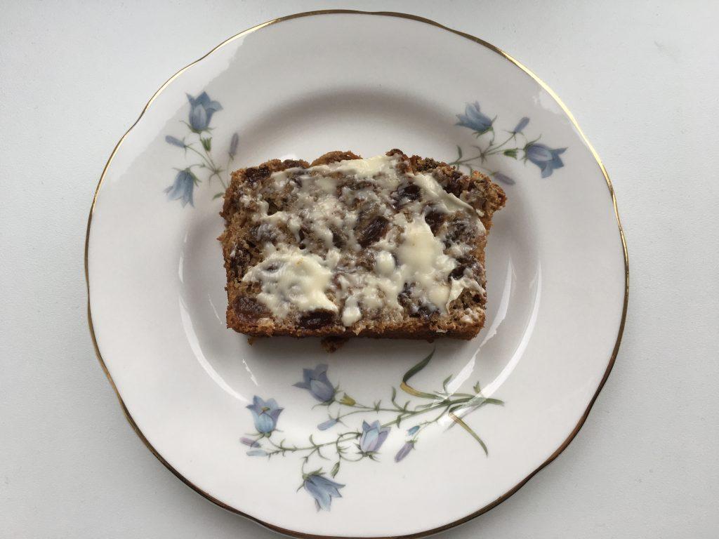A slice of gluten free tea loaf spread with Lurpak butter.