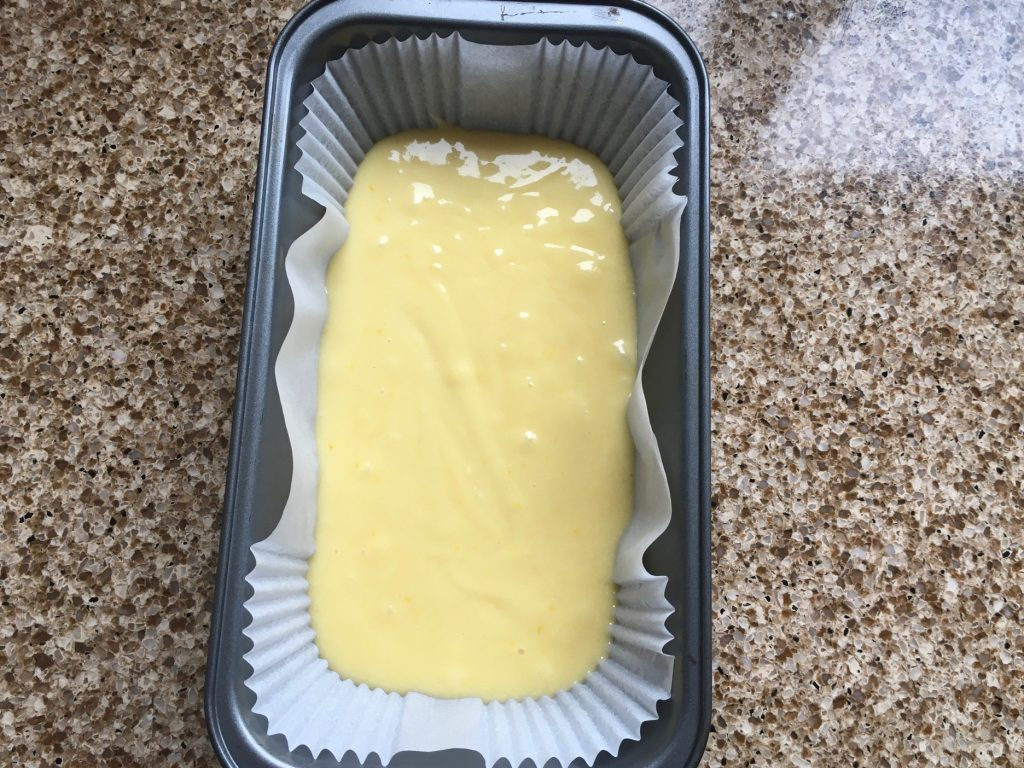 Lemon drizzle cake mixture in a loaf tin ready to bake.
