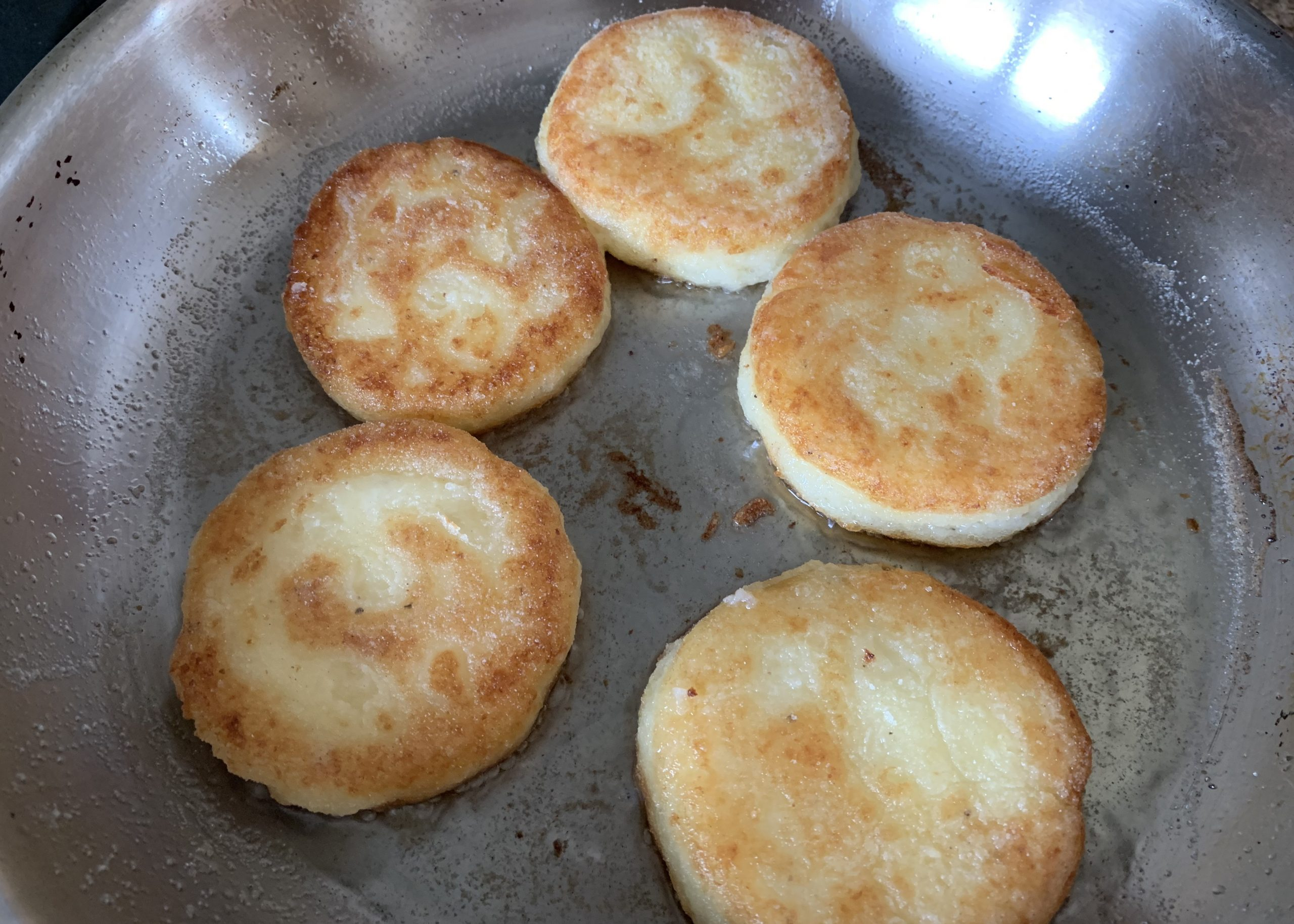 Gluten free potato cakes cooking in a frying pan