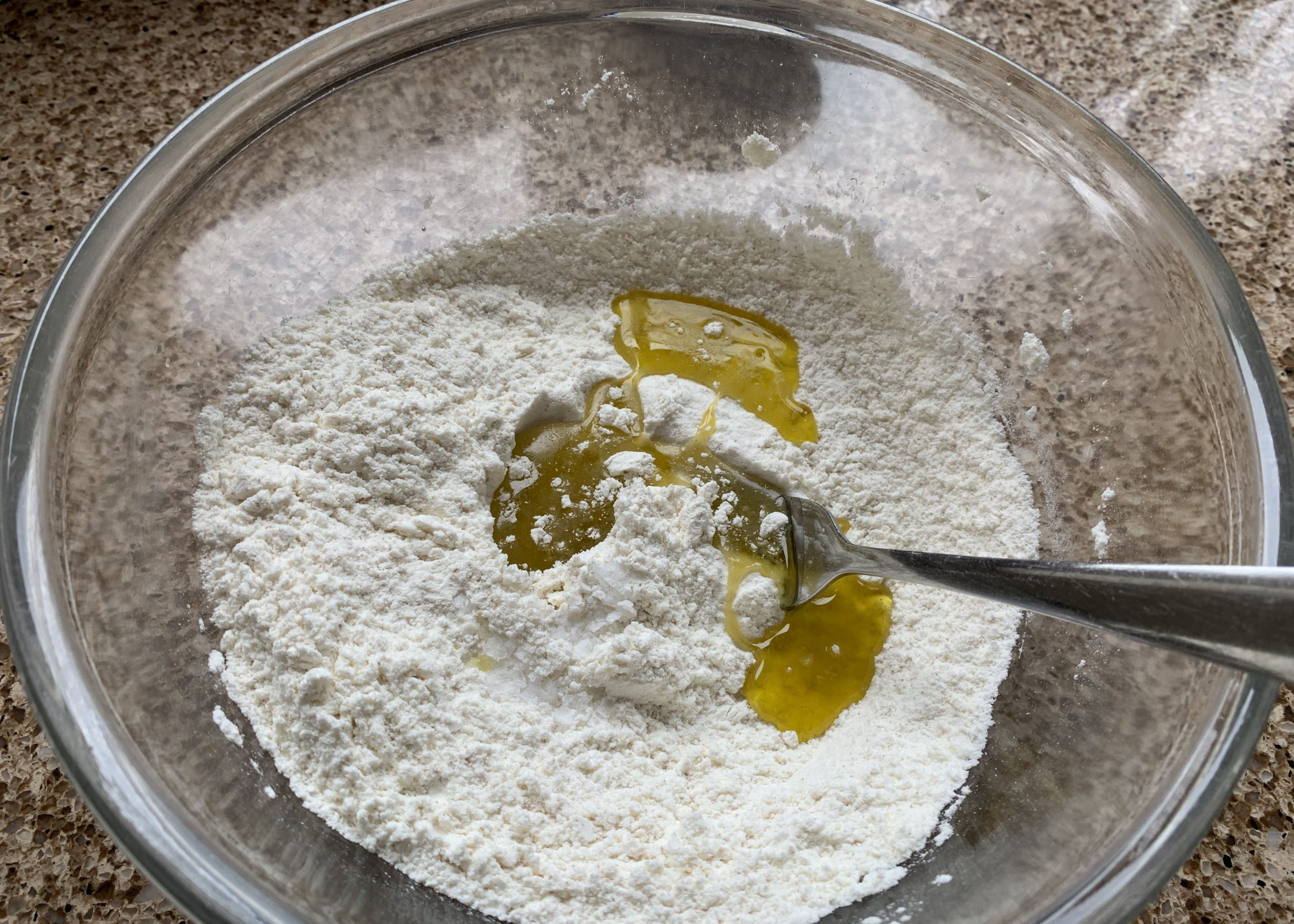 Ingredients in a glass bowl for gluten free pizza base