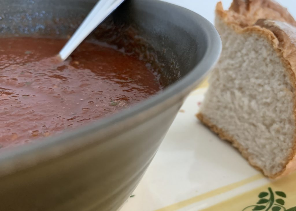 Soup in a bowl with a chunk of gluten free bread