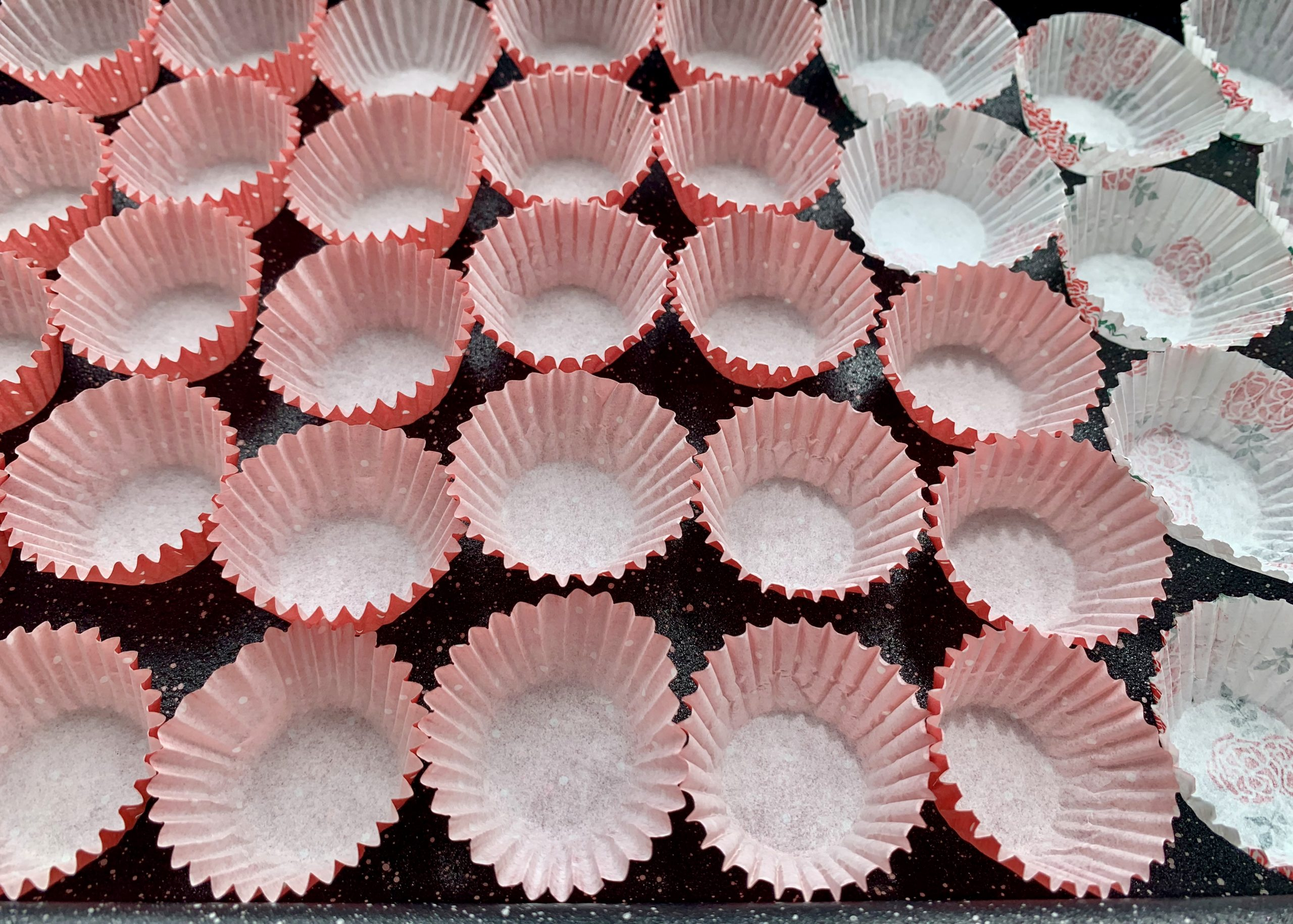Petit four cases lined up on a baking tray