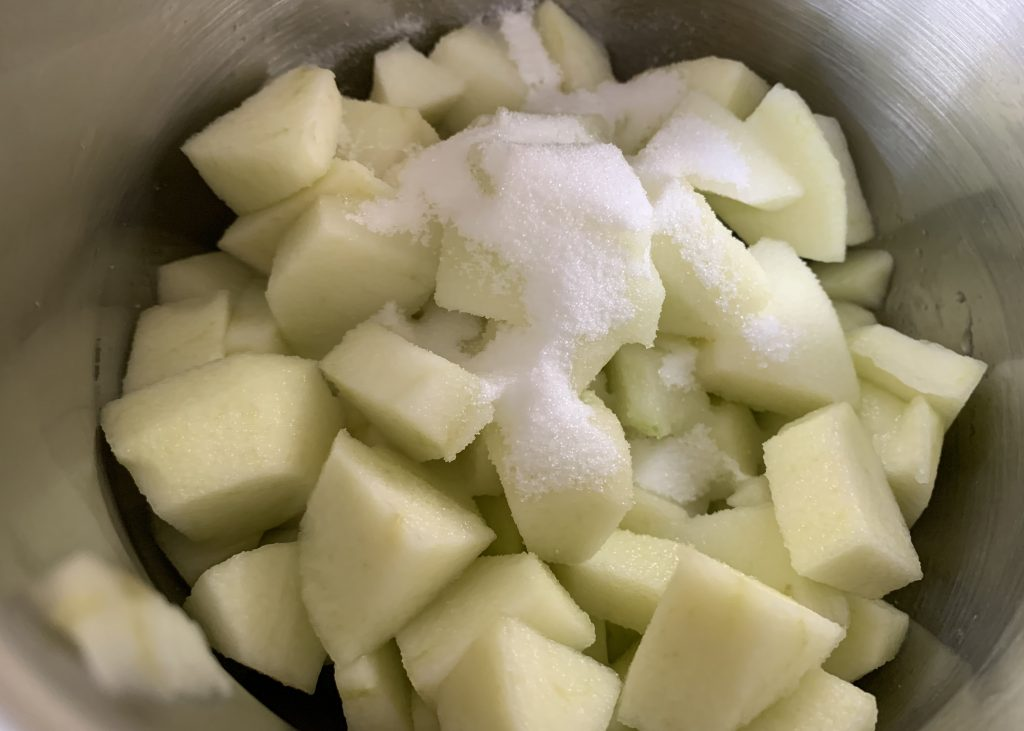 Diced brambly apples in a pan with sugar