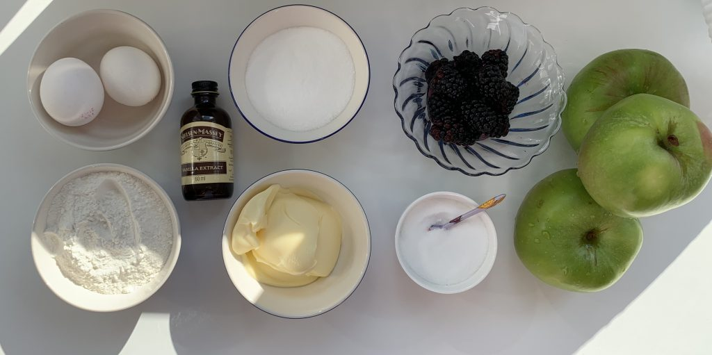 Flatlay of ingredients for gluten free Eves pudding with blackberries and apples